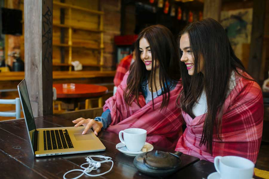 Two women in a coffee shop browsing the internet